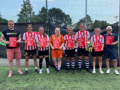 Exeter City A, women's winners of the Exeter City FC One Game One Community Group community diversity football tournament, with Simon Kitchen from ECFC OGOC group, left and Kevin Hack, tournament director, right.