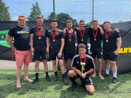 Marcel's Allstars, men's winners of the Exeter City FC One Game One Community Group community diversity football tournament, with Simon Kitchen from ECFC OGOC group, left. Photo: Alan Quick