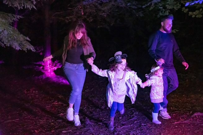 Two adults and two children run through trees in the dark