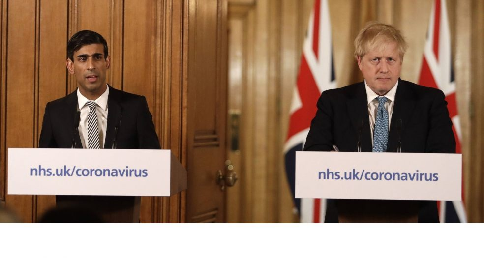 Boris Johnson looking unhappy at a press conference, accompanied by Rishi Sunak