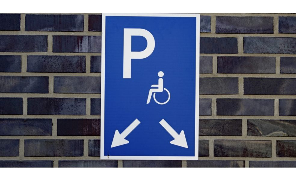 Disabled parking sign pointing at parking spaces on a grey brick wall