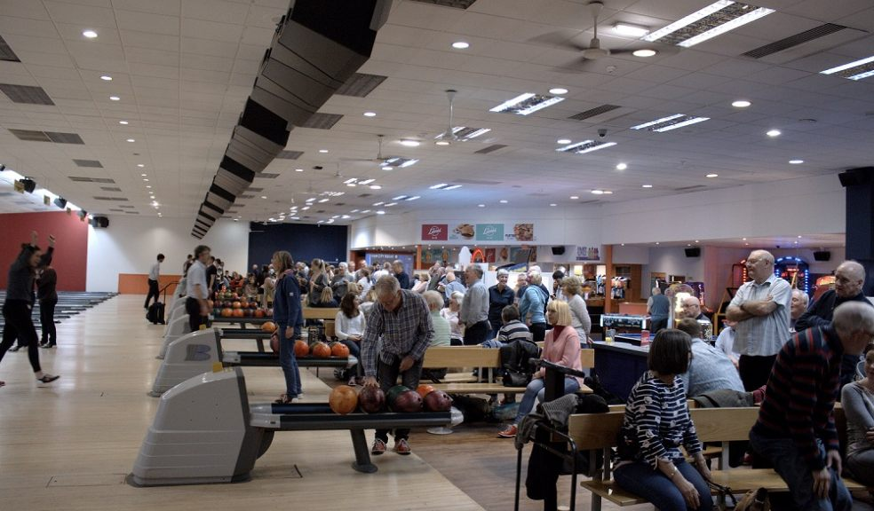 Lots of people bowling in a bowling alley