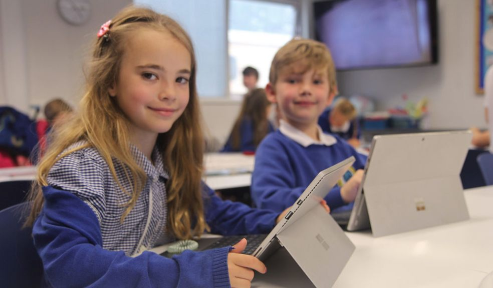 Two Westclyst Community Primary School pupils with their laptops in class