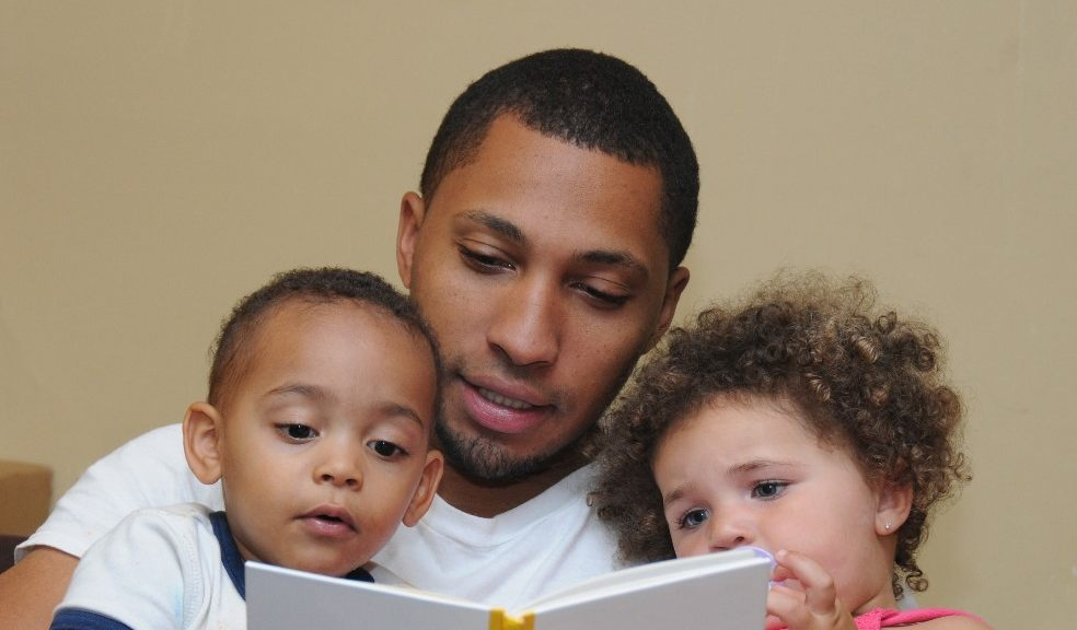 Photograph showing a man reading a book to two children