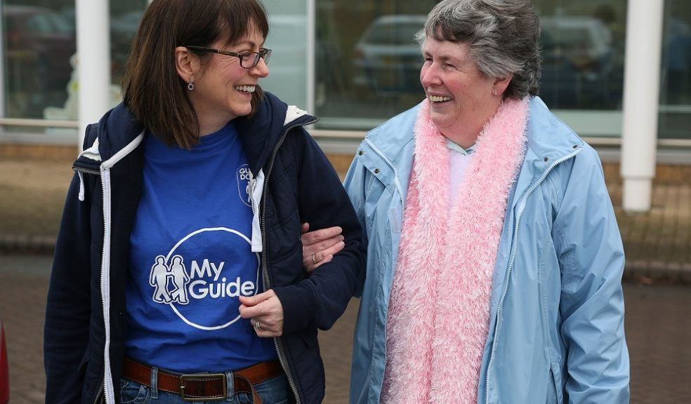 two women walking together chatting and laughing, one provides on arm guiding, the other is visually impaired