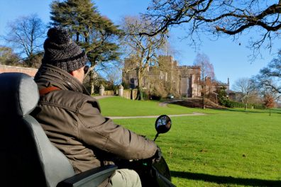 User of mobility scooter with Powderham Castle in the background