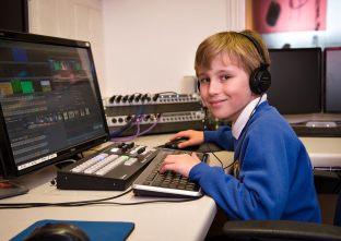 Year 4 BCPS student using desktop computer and headphones