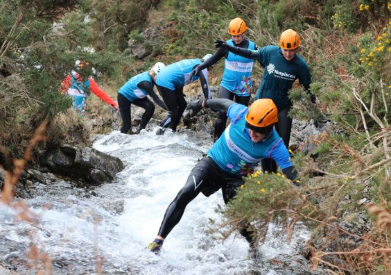 People in Hospiscare t-shirts scramble through a gorge
