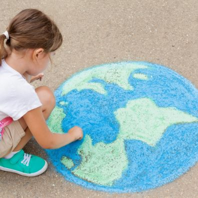 A girl draws a planet of the world with colored chalk on the asphalt. Children's drawings, paintings and concepts. Education and art, be creative when you return to school. earth, Peace day. jpg  PICTURE: Getty Images/iStockphoto