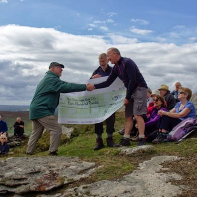 Devon Ramblers chairman Andrew Chadwick presents £500 cheque to Dartmoor Way project manager Michael Owen at the 50th anniversary celebration picnic on Hookney Tor (photo credit: Peter Walker)