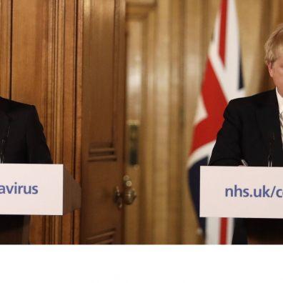 Boris Johnson looking unhappy at a press conference, accompanied by Rishi Sunak