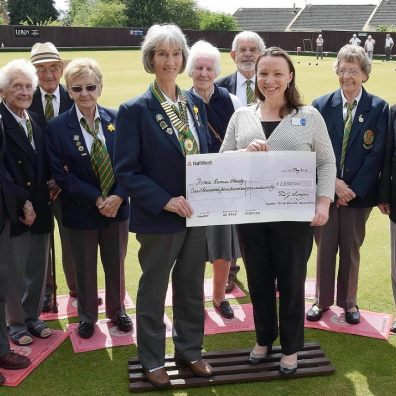 Nomads bowlers present a cheque for £1,500 to FORCE Cancer Charity