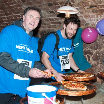 Men's Walk participants in Hospiscare t-shirts enjoy a pizza en route